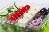 Fresh greek salad in plastic bowl — Stock Photo