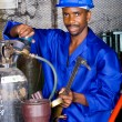 African american industrial welder in workshop with gas welding gears — Stock Photo