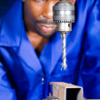 African blue collar worker in workshop working on drilling machine — Stock Photo #14754129