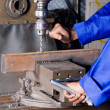 Operator working on industrial drilling machine in workshop - Stock Photo