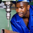 African american factory worker working on industrial drilling machine — Stock Photo #14754137