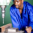 African industrial machinist working in workshop — Stock Photo