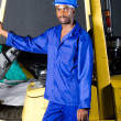 Stock Photo: Africforklift driver standing next to forklift