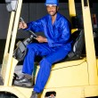Stock Photo: African american industrial forklift driver on forklift