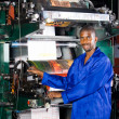 Stock Photo: African printing press operator in factory
