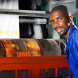 African plastic bag printing machine operator at work — Stock Photo