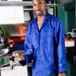 African printing machine operator standing next to printing press — Stock Photo