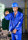 African american machinist standing next to a drilling machine — Stock Photo