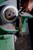 Man working on grinding machine with metalwork — Stock Photo