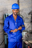 Young african factory working in workshop with hammer — Stock fotografie