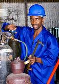 African american industrial welder in workshop with gas welding gears — Stock Photo