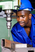 African american factory worker working on industrial drilling machine — Stock Photo