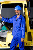 African forklift driver standing next to a forklift — Stock Photo