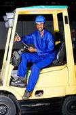 Afroamerikanska industriella truckföraren på gaffeltruck — Stockfoto