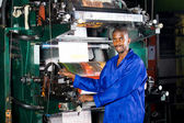 African printing press operator in factory — Stock Photo