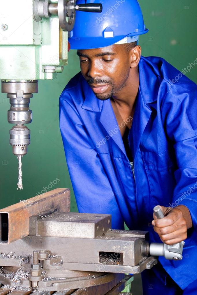 African industrial machinist working in workshop — Stock Photo #14754145