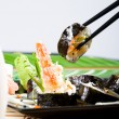 Chopsticks picking up sushi roll — Stock Photo