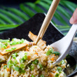 Eating chinese stir fry rice with chopsticks and spoon — Stock Photo