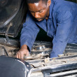 Stock Photo: African mechanic working on a broken down vehicle