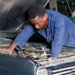 African american mechanic repairing vehicle - Stock Photo