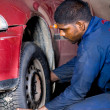 Mechanic changing vehicle tyre — Stock Photo