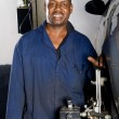 African american auto mechanic working on a vehicle wheel alignment — Stock Photo