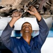 African american mechanic working on a broken down vehicle - Stock Photo