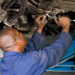 Stock Photo: Africamericmechanic repairing car