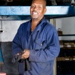 African auto teachnician in garage - Stock Photo