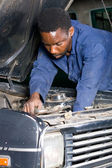 African mechanic working on a broken down vehicle — Stock Photo