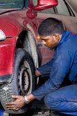 Mechanic changing vehicle tyre — Stock Photo