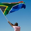 African man waving a south african flag against blue sky — Stock Photo