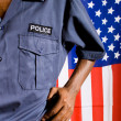 Police officer, background is american flag — Photo