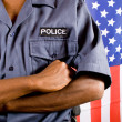 African american policeman standing in front of USA flag - Stock Photo