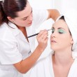 Professional female makeup artist applying makeup to model's face — Stock Photo #14817615