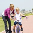 Happy mother teaching little daughter how to ride a bicycle — ストック写真