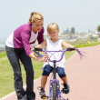 Happy mother teaching little daughter how to ride a bicycle — Stockfoto