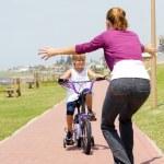 快乐的小女孩骑着自行车往她的母亲 — 图库照片