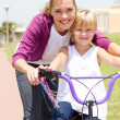 Stock Photo: Happy mother teaching little daughter how to ride a bicycle