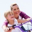 Low angel view of happy mother teaching daughter how to ride a bicycle — Stock Photo
