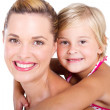 Happy little girl piggyback with her mother, — Stockfoto
