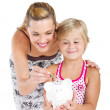 Happy mother putting coins into her daughter's piggybank — Stock Photo #14818565