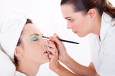 Professional female makeup artist applying makeup to model's face — Stok fotoğraf