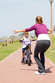 Happy little girl riding a bike toward her mother — Stock Photo