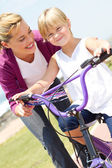 Happy mother teaching little daughter how to ride a bicycle — Stock Photo