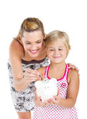 Happy mother putting coins into her daughter's piggybank — Stock Photo