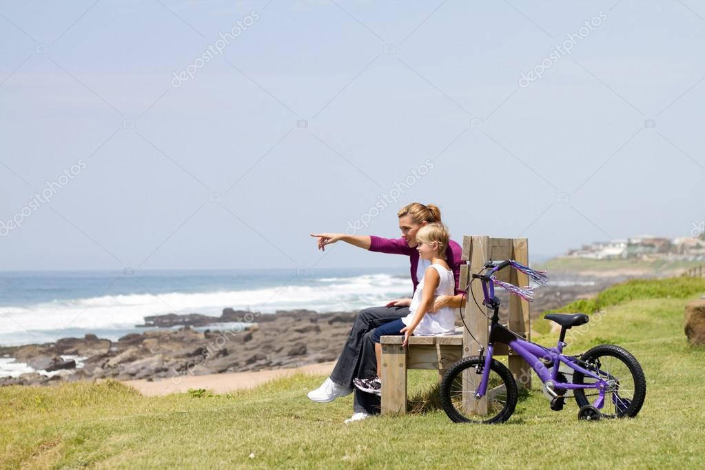 Young mother and little daughter sitting on beach bench — Stock Photo #14818179