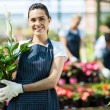 Stockfoto: Happy female nursery owner with pot of flowers inside greenhouse
