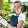 Happy female nursery worker in greenhouse — Stock Photo