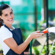 Pretty florist watering flowers in greenhouse — Stock Photo #14899861
